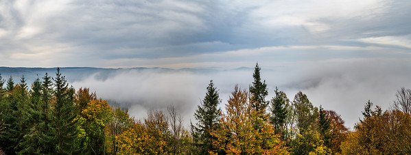 Panoramic view from the mountain in the fall. A sea of fog spreads between the mountains.