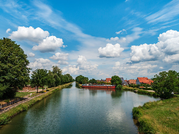 An idyllic picture of the Rhone and Rhine Canal on a warm, windless summer day, with clouds floating across the blue sky