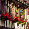 Classic Alsatian windows in a half-timbered house, decorated with wooden carvings and flowers