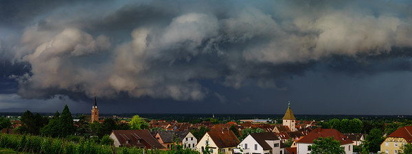 Dark sky, overcast, black clouds. Stormy weather over the village Bergheim. Panoramic view.