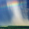 Beautiful rainbow with rainy clouds, colorful summer view