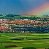Colorful rainbow over the green fields and vineyards