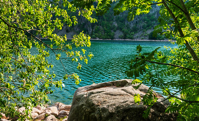Emerald-colored water in a calm mountain lake in the Vosges. Calmness and pacification.