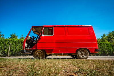 Old retro red minibus on blue sky background