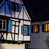 Glowing warm homely windows in a small Alsatian village. Comfort and warmth at home on a winter evening.