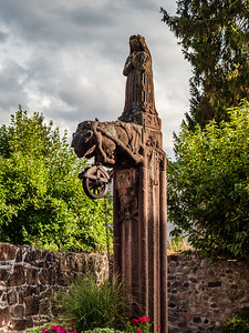Medieval stone statue over an old well, Alsace, territory of Andlau Abbey