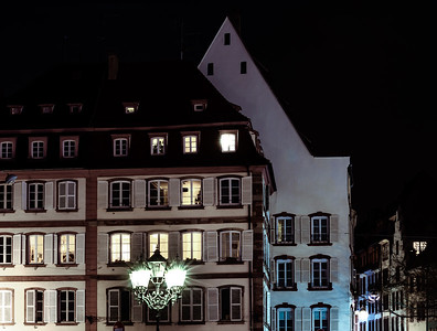 Street lamp and buildings with highlighted windows, night view of Strasbourg