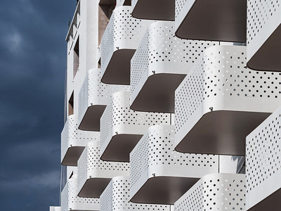 New modern home. Balconies on the facade of the building create a beautiful pattern. Strong contrast of a white building with a dark stormy sky.