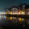 Ile River Embankment in Strasbourg at night, fog. Reflections of illuminated buildings and lanterns in the water