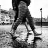 Rain in the city. People walk barefoot on the asphalt. Splashes and drops.