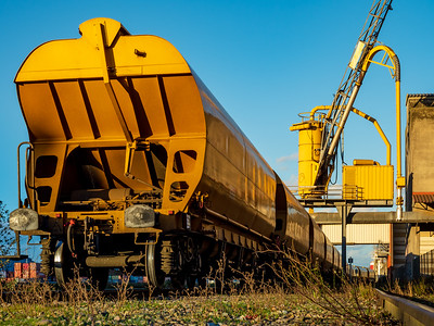 Bright yellow railway freight car against the blue sky in the port of Strasbourg.