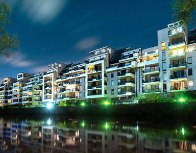 New modern apartment house on the city pond in Strasbourg, night view with reflection in the water