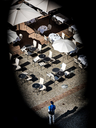 An overhead view of the empty tables and umbrellas of a street cafe in front of the cathedral in the tourist center of Strasbourg.