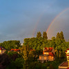 Stunning double rainbow over the tiled roofs of houses after rain