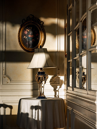 The rich interior of the palace. Beautiful table lamp , sunny shadows