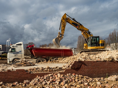An excavator breaks down an old building. Dust, bricks and broken walls.