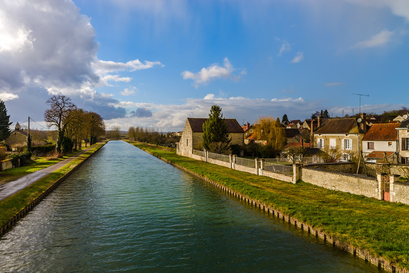 Green water of canal and blue sky, springtime in countryside
