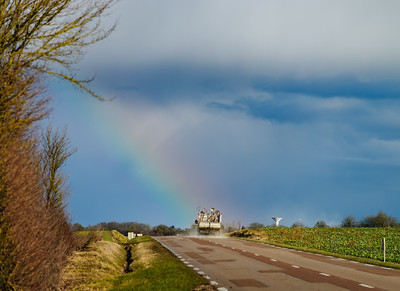 Beautiful colorful rainbow at the end of asphalt road, perspective view