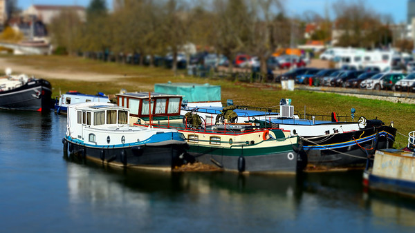 Old colorful little ships on the river in Auxerre