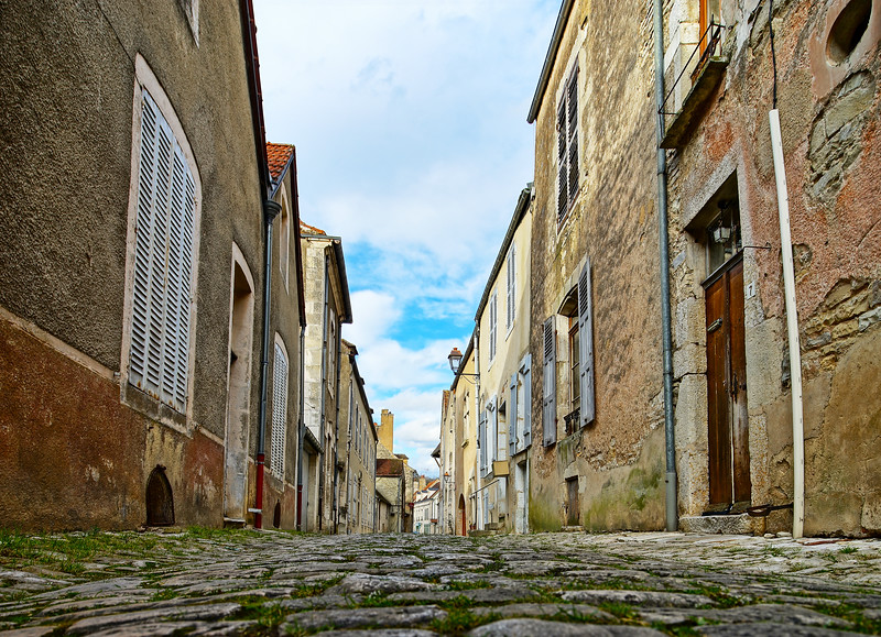 Old medieval houses on the cobbled street in ancient french village Noyers