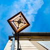 Old-styled street lamp on the wall of old house, on blue sky background