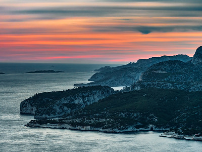 A bright red sunset over the sea in Cassis, on the French Riviera. View from the mountain to the sun falling into the water. Calanques and promenade in the city.