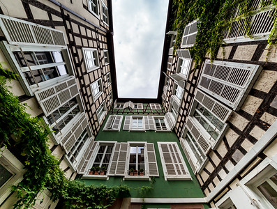 Well-yard in Paris. Classic houses with tall windows and old shutters. Walls overgrown with plants. The narrow courtyard of an ordinary house.
