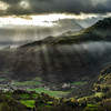 Sun rays lighting through the clouds in high Pyrenees, sunrise, green valley