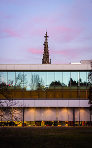 Abstract composition of new modern glass building and church tower, sunset