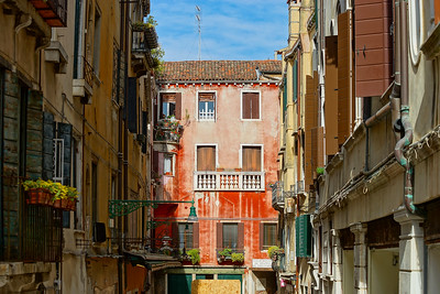 Tourist view of Venice. Channels with reflections. Street lights and colorful houses in the bright sun. Comfort and tranquility.