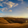 Sunset over the unending tuscany hills, Yellow slopes and blue sky, vivid colors,
