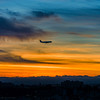 Airplane silhouette on sunset sky background