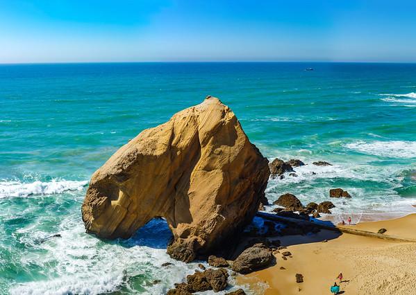 Yellow rocks and sand on portuguese coastline, vivid ocean water