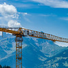 Yellow constructing crane on mountains background, Alps Switzerland