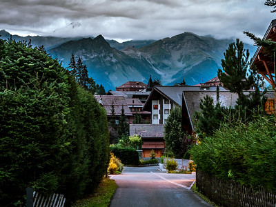 Evening street view in a small Swiss village. The high Alps in the background seem to be drawn. Warm lighting of cozy chalets.