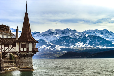 Oberhofen castle tower on alpine background, mountains with snow, Switzerland