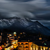 Clouds floating over mountain alpine peaks in the late evening, an atmosphere of darkness and beauty
