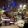 Snow-covered street cafe tables on winter street, Strasbourg, Christmas time. Night scene with highlighted old buildings. Tourisitic concept.