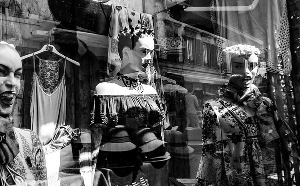 Combined view in shop glass wall with mannequins and street reflections