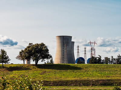 Nuclear power plant in France. Huge chimneys rise above the sunny landscape.