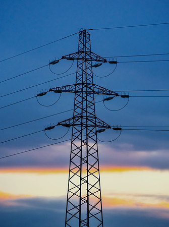 Power line mast against the background of the sunset sky