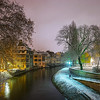 Old timber-framing houses in Petite France quarter, Strasbourg. Snow-covered roofs and refctions in the river water. Night scene.
