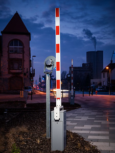 Lighted railroad crossing at night. Open barriers.