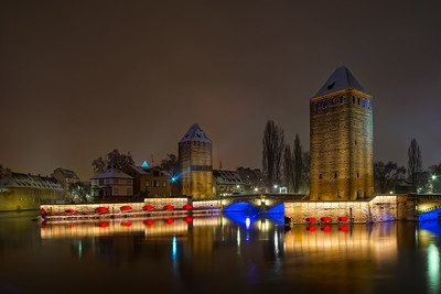 Night view of highlighted medieval towers in Strasbourg with reflections in the water
