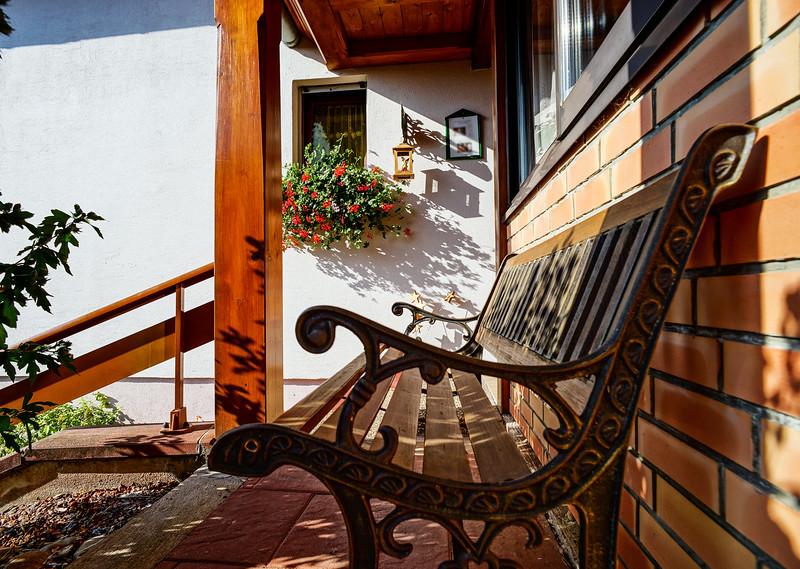 Elegant bench near the house, sunny day