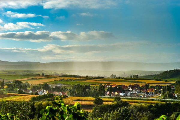 Rainy weather over the green valley in Alsace, sun shining and water falling down