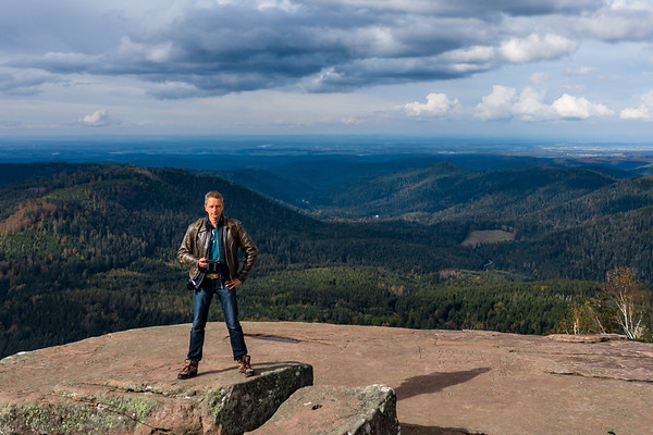 A man controls a drone standing on top of a cliff. Around the autumn mountain landscape. Vosges, Alsace.
