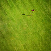 Green golf field with flag aerial view from drone
