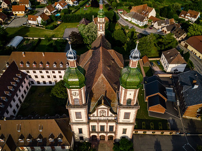 Soaring majestic church Saint Maurice in little french village Ebersmunster. Aerial drone view.