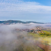 A drone view of the stunning expanse of the Vosges foothills. Autumn vineyards in the morning fog.